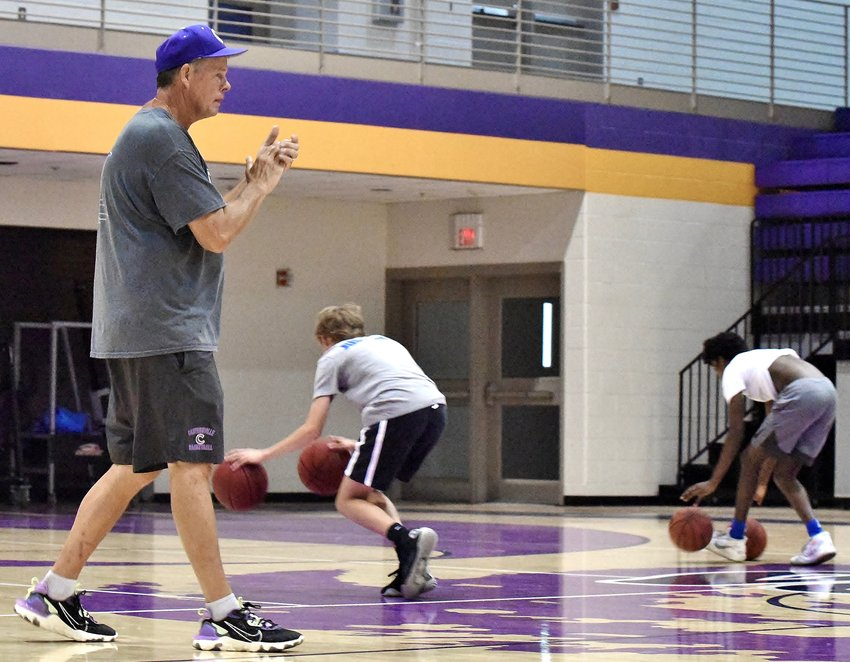 Cartersville head boys basketball coach Mike Tobin, left, encourages his players through a dribbling drill during Monday's workout inside The Storm Center.
