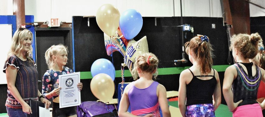 Sydney Jackson, second from left, shows her fellow gymnasts her Guinness World Record certificate. Sydney's mother, Heather, left, looks on.