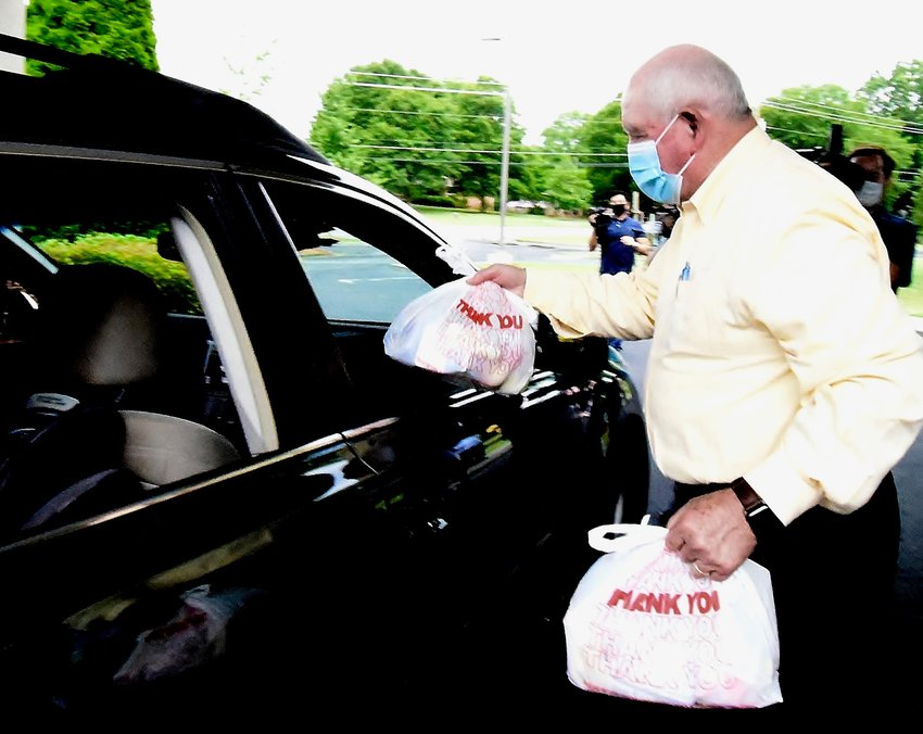 U.S. Secretary of Agriculture Sonny Perdue hands bagged lunches to recipients of school meals at Faith United Methodist Church Thursday.