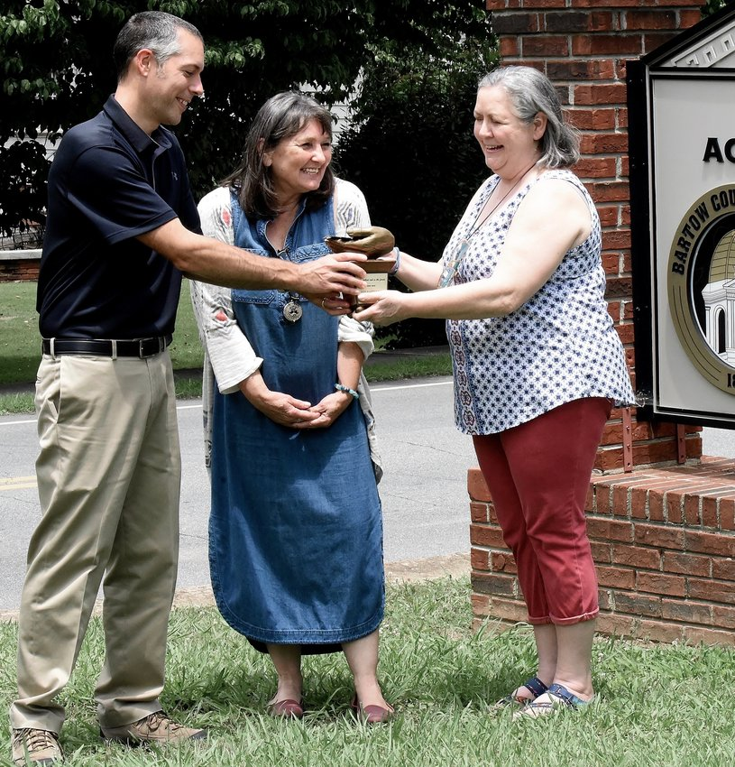 As Keep Bartow Beautiful Executive Director Missy Phillips, center, looks on, Bartow County Extension Coordinator Paul Pugliese presents retired KBB Executive Director Sheri Henshaw a retirement gift of bronze hands holding oak leaves and an acorn. The hands are a KBB tradition.