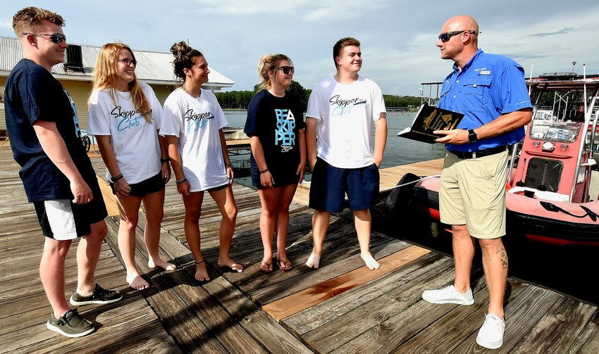 Chris Day, right, owner of Georgia Boat Safety and Training, reviews material pertaining to the Skipper Club with Skipper Club ambassadors, from left, Carter Bradford, A.J. Keeler, Kat Zitzmann, Taylor Day and Clayton Vliegenthart.