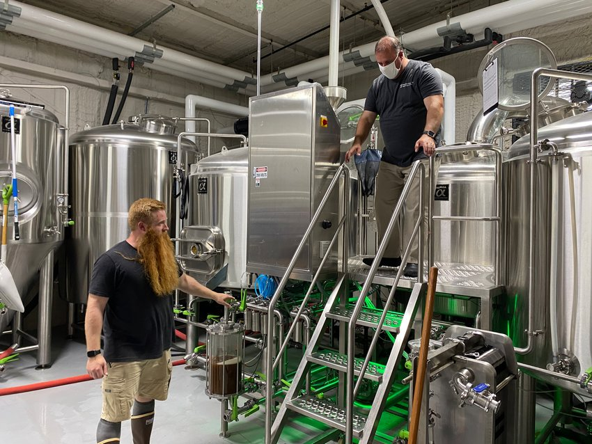 JD Dean, Drowned Valley Brewing's head brewer, assists Cartersville Mayor Matt Santini, right, in creating a new beer to raise funds for the United Way of Bartow County.