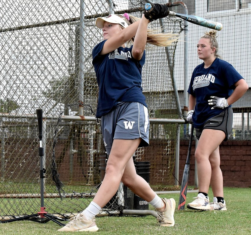 Woodland senior Ansley Evans, left, hits off a tee as classmate Hannah Miller watches during practice Friday.