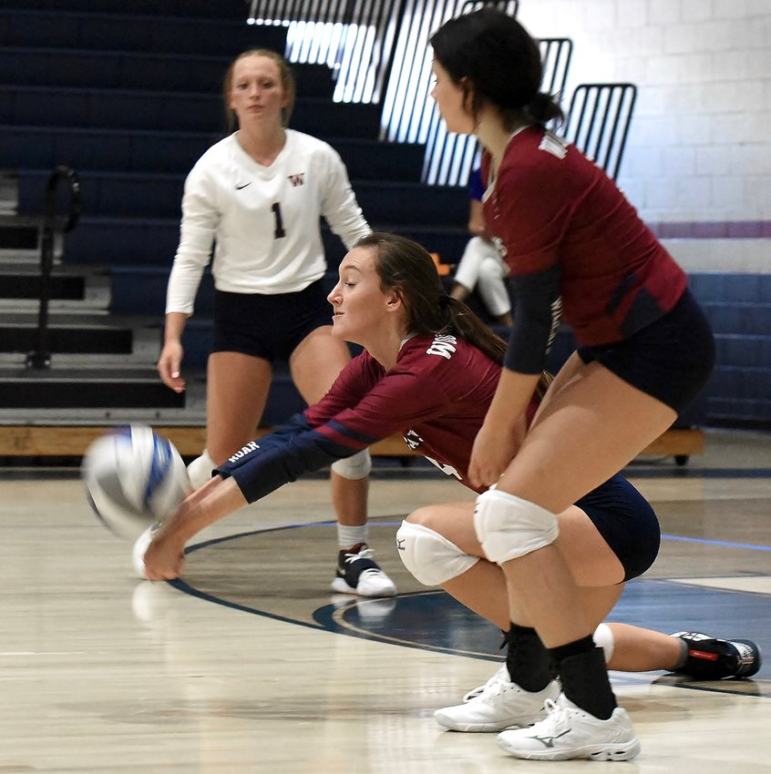 Woodland junior Delaney Tuplin, center, digs the ball during a match against Model Thursday at home.