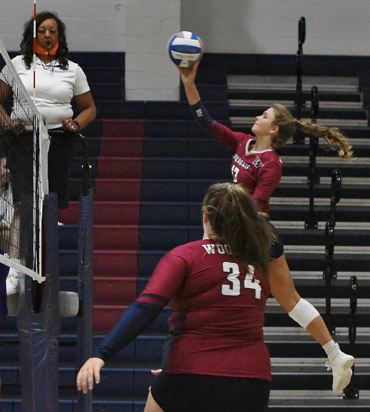 Woodland senior Sydney Molinaro (13) tips the ball over the net as sophomore teammate Kailynn Mullinax looks on during Thursday's home match against Darlington.