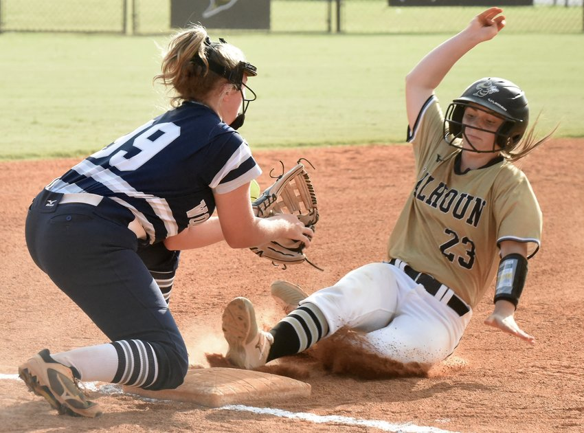 Calhoun's Paris Kirby slides safely into third base as Woodland's Hannah Miller can't cleanly field a throw from catcher Kailey Baker. Kirby and the Yellow Jackets swept the Wildcats — 6-5 and 7-3 — during a Region 7-AAAAA doubleheader Thursday in Calhoun.