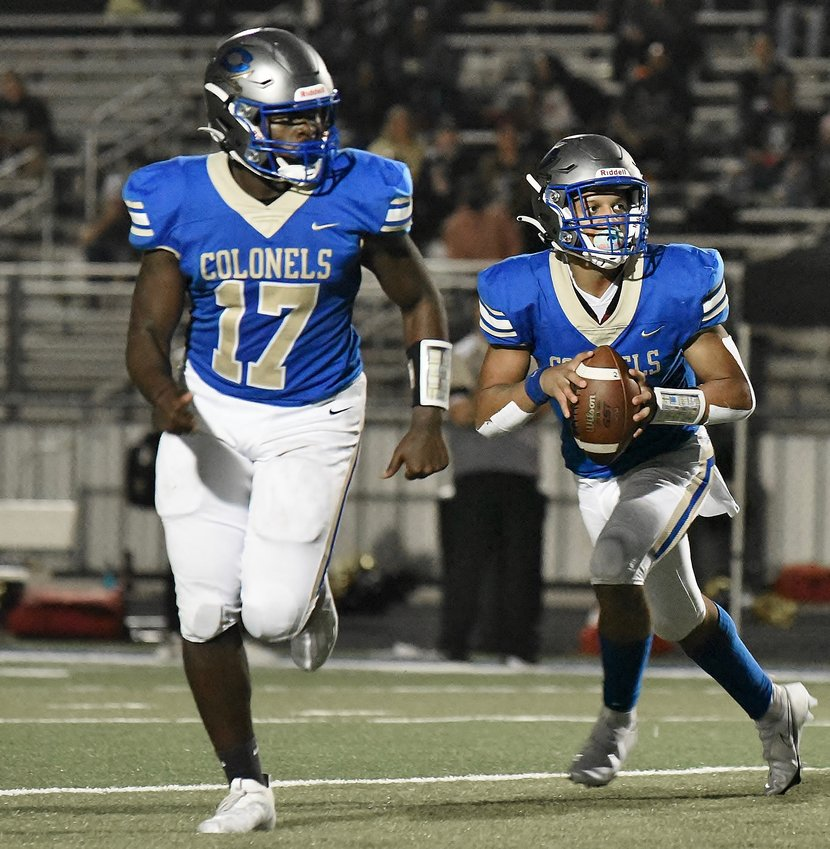 Cass freshman quarterback Devin Henderson rolls out to pass as Josh Varnum (17) runs to the flat during Friday's win over Temple.