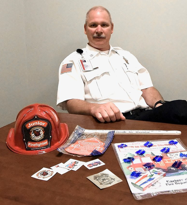 Cartersville Fire Marshal Mark Hathaway displays examples of public education items that will be purchased with funds raised from the department's October virtual boot drive.