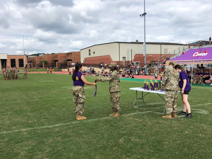 Cadet Lt. Col. Jai Smith, right, presents a streamer to cadet Tashelly Nagamine, captain of the female Alpha team, at the end of Cartersville High JROTC's first Hurricane Raider Challenge last month.