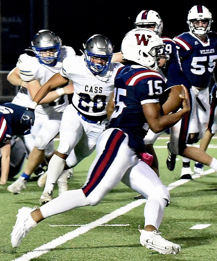 """Woodland senior quarterback Johnathan Thomas carries the ball against Cass during last week's game at Wildcat Stadium. After leaving with an injury last week, Thomas is considered a """"game-time decision"""" against Calhoun this week."""