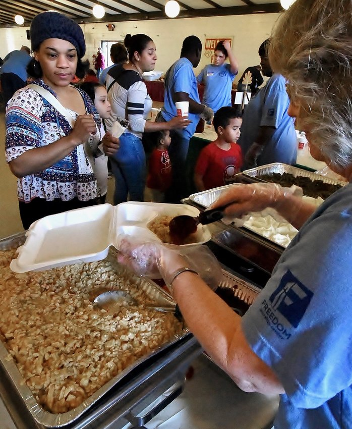 Volunteers serve food to community members at the 2019 Feed Bartow event at the Cartersville Civic Center. Due to COVID-19, this year's offering will consist of a drive-thru distribution of boxed read-to-cook meal kits Sunday.