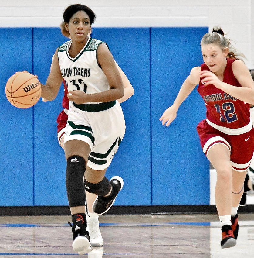 Adairsville's Autumn Henderson dribbles up the court as Woodland's Ansley Evans gives chase during a tournament game Monday at Armuchee. Henderson scored 15 points, including the go-ahead 3-point play in the final seconds, in a 51-49 victory.