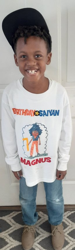 Cartersville Primary first-grader Magnus Smith shows off a shirt bearing one of his drawings of Super Saiyan Goku from Dragon Ball Z on his seventh birthday in October.