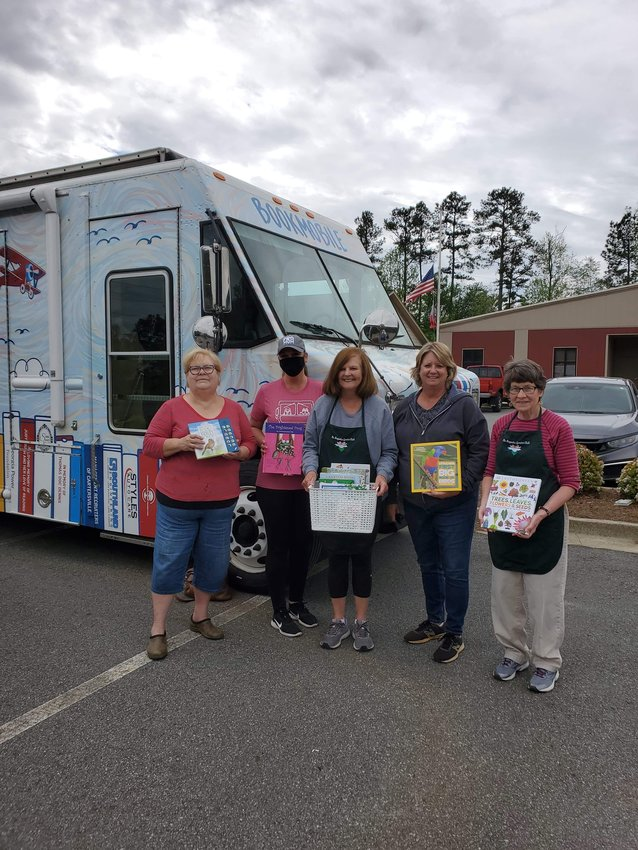 Several Magnolia Garden Club members donate books highlighting gardening and birds to The Bookmobile Saturday.