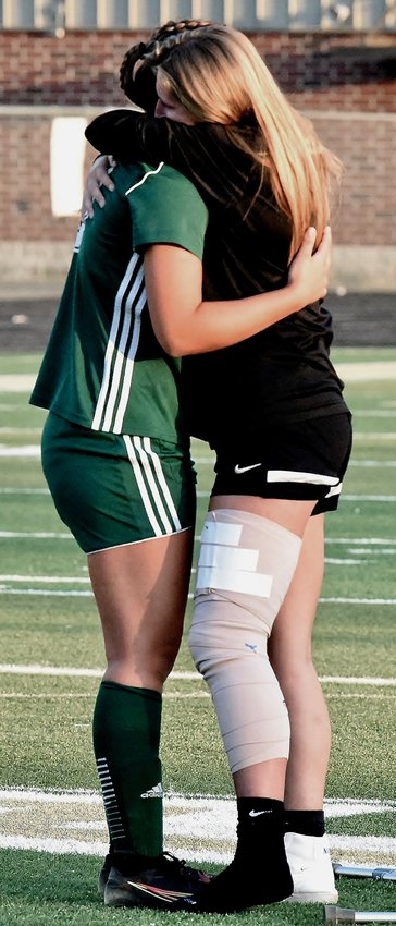 Adairsville seniors Sadye Johnson, left, and Cat Wheeler hug at the conclusion of a 2-0 loss to North Hall in the first round of the Class 3A state tournament Tuesday at Tiger Stadium. Wheeler missed the match after suffering a knee injury in the team's regular-season finale.