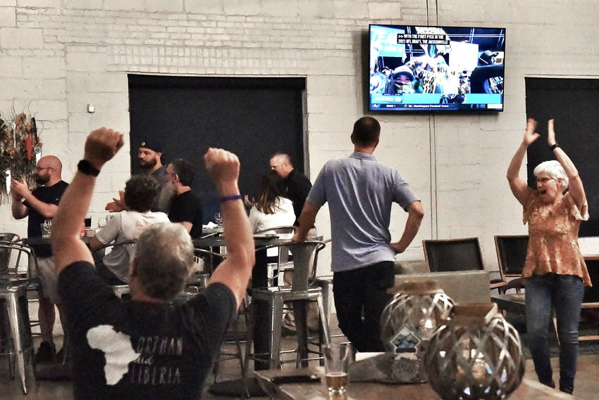 Trevor Lawrence fans celebrate the announcement of him being selected first overall in the NFL draft by the Jacksonville Jaguars Thursday night at Drowned Valley Brewing Co. in Cartersville.