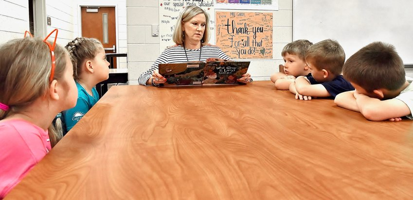 RANDY PARKER/THE DAILY TRIBUNE NEWS Retiring Cloverleaf Elementary Principal Dr. Evie Barge reads to, from left, first-graders Julianna McSwain and Georgia Beaver and kindergartners Judd Willingham, Liam Simpson and Grayson Stover.