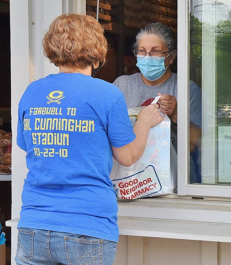 Karen Tindall, right, hands a bag of food to a recipient of the Red Door Food Pantry in Cartersville.
