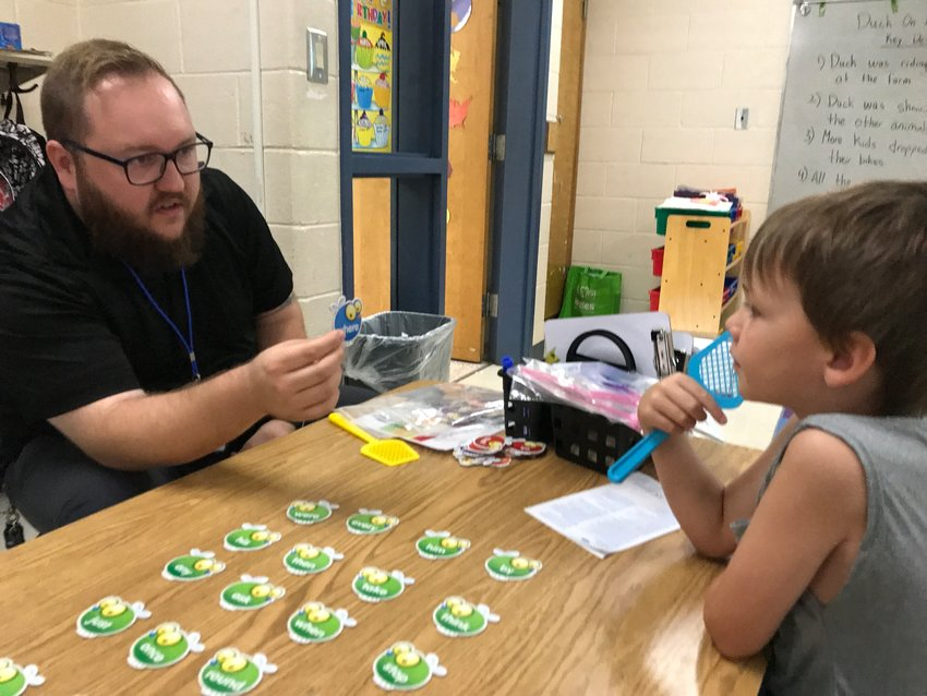 Read to Grow volunteer Adam McEntyre helps Allatoona Elementary third-grader Jordan Brown with his sight words during one of their weekly sessions last year.