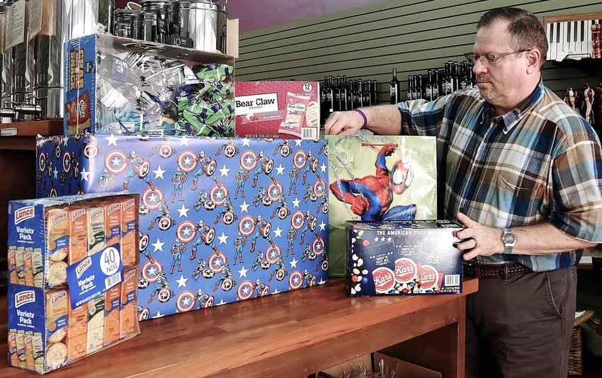 Darrell Waits-Shead arranges Snacks for Superheroes donations at Olive Tree and Vine in Cartersville.