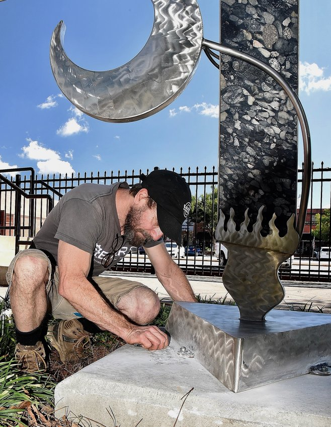 """Ellijay sculptor Eric Strauss reinstalls """"Elements of Reason"""" at Friendship Plaza in downtown Cartersville Sept. 9. The sculpture received significant damage during a storm in October 2020."""