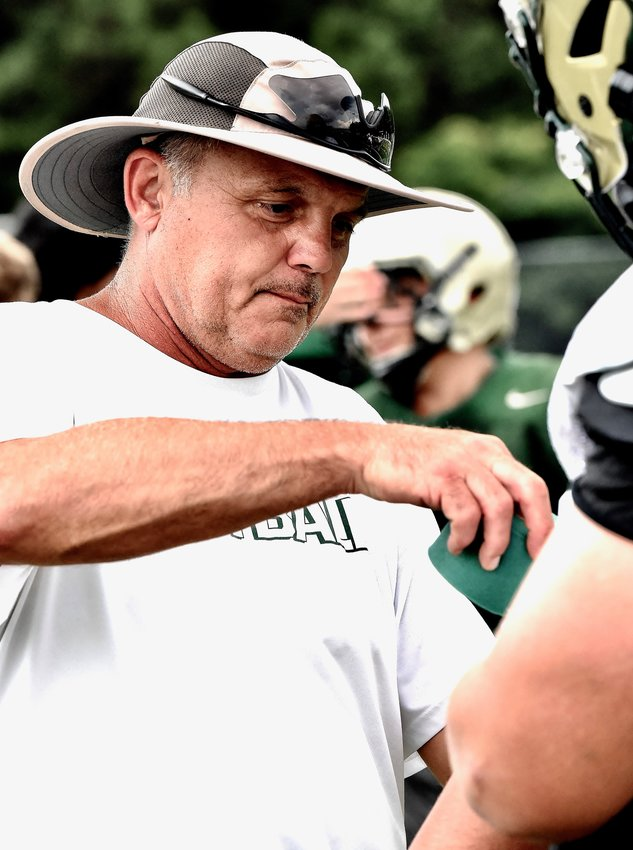 Adairsville head coach Eric Bishop helps adjust equipment for one of his players during a practice in early August at Tiger Stadium. Bishop and Co. will host LaFayette this week.
