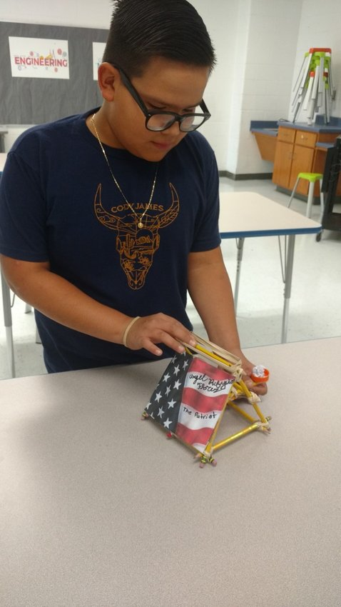 Woodland Middle sixth-grader Angel Flores demonstrates the catapult, named The Patriot, that he made from pencils.