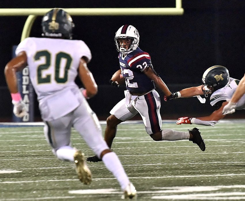 Woodland senior Asa James shakes off a tackle attempt and looks for additional running room during a Region 7-5A game against Blessed Trinity Thursday at Wildcat Stadium.