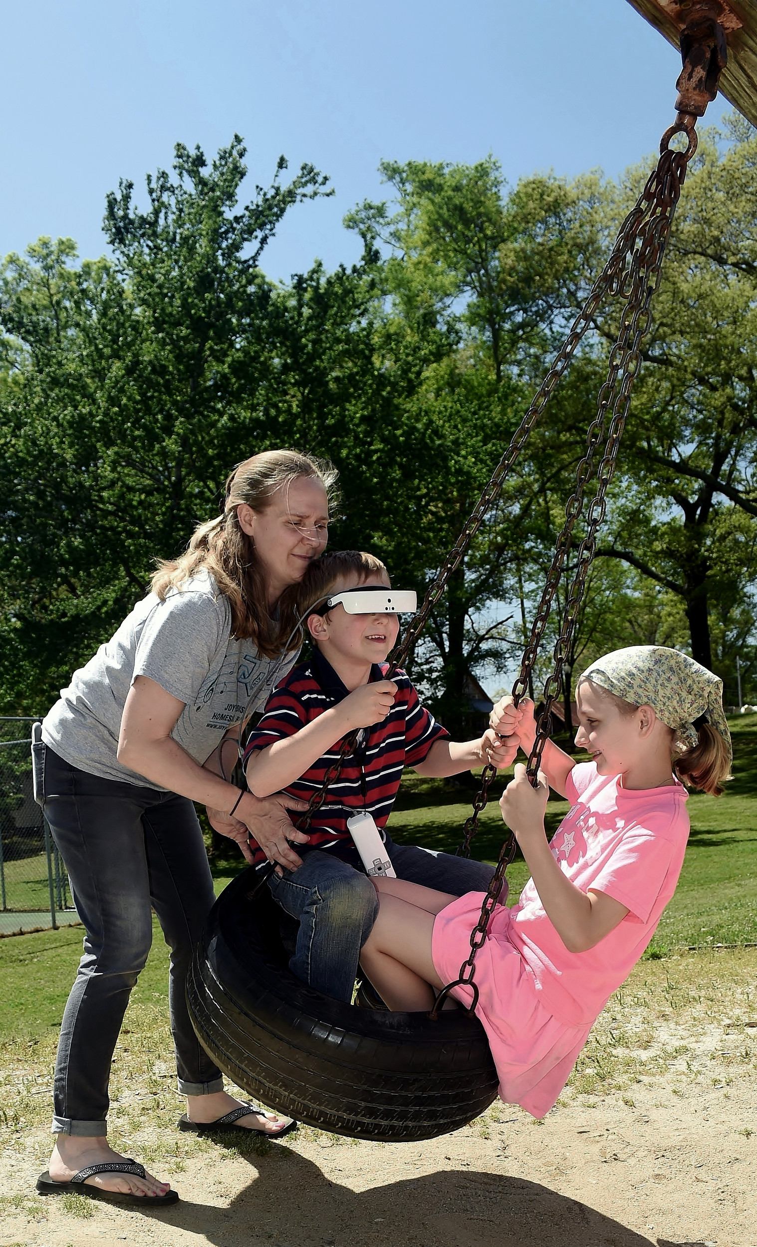 Chrysti Goltz pushes her children Malachi and Victoria in a tire swing at Osborne Park in Euharlee Wednesday.