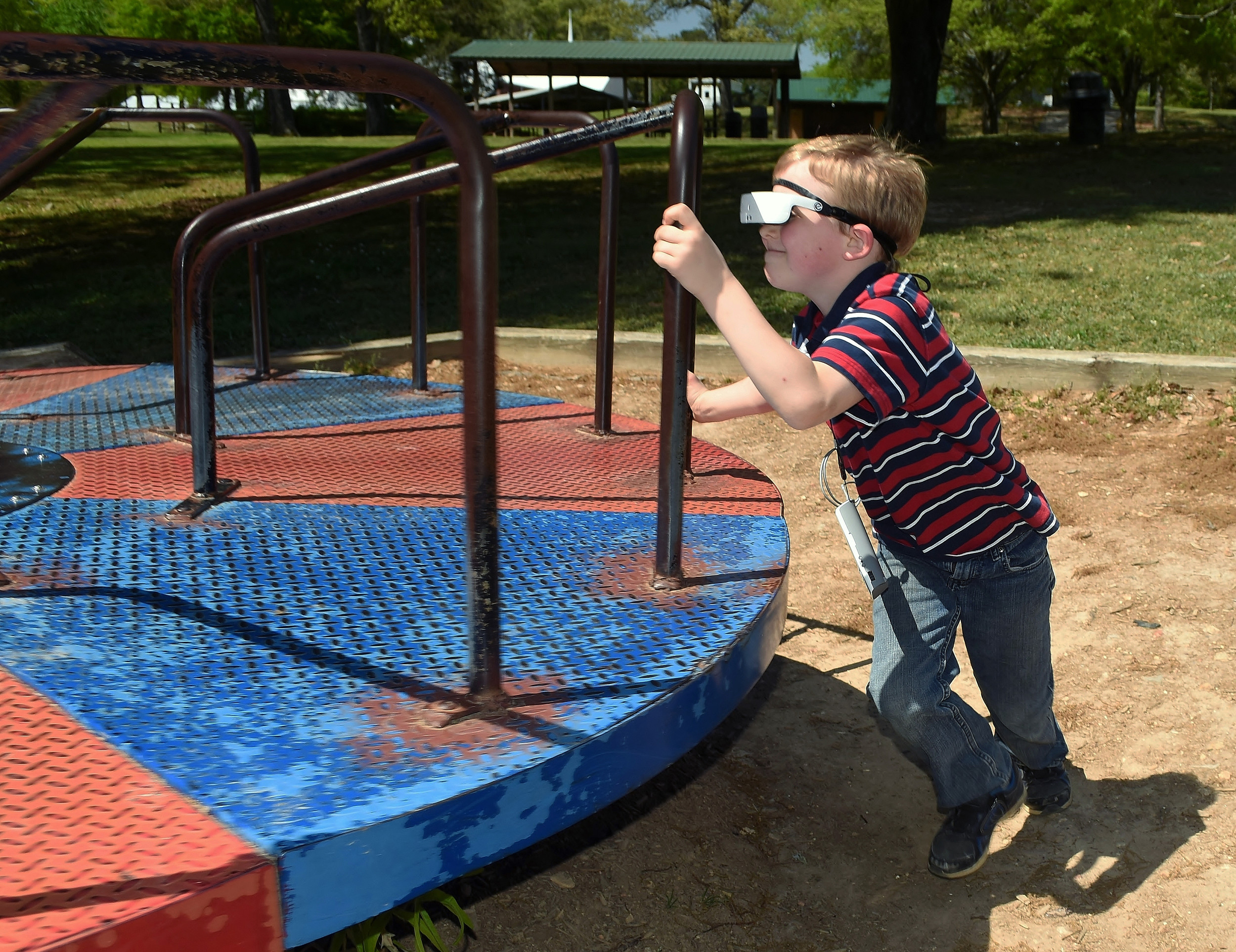 Wearing his eSight glasses, Malachi Goltz spins the carousel at Euharlee's Osborne Park.