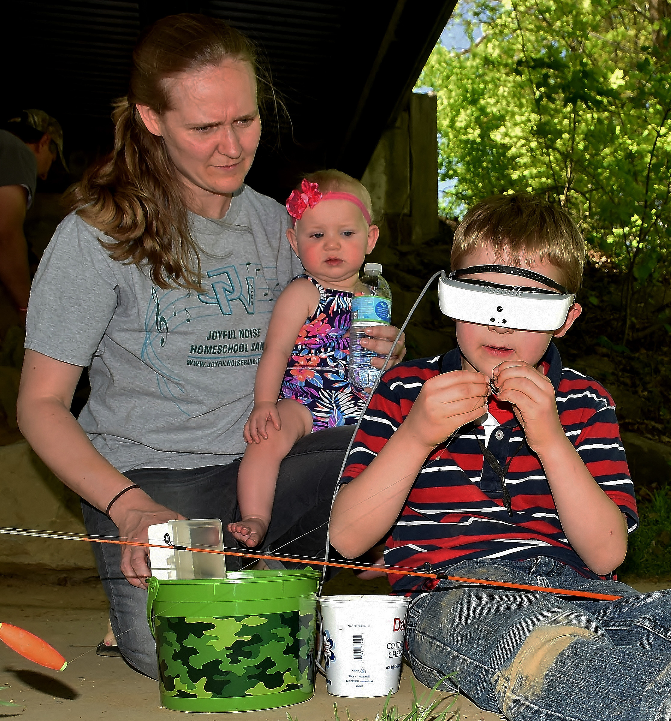 Using his eSight eyewear, Malachi Goltz baits his fishing hook as his mother, Chrysti, and sister Ivy look on.