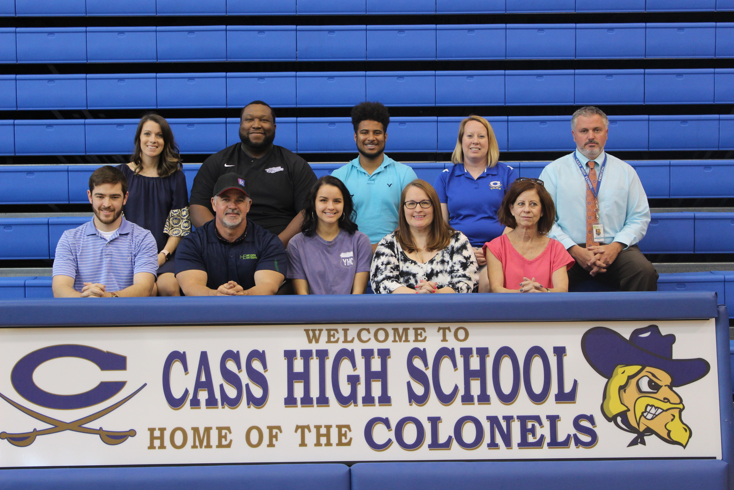 Cass senior Siarra Swanson, center, signed with the Young Harris competitive cheer squad Wednesday in the high school's gym. On hand for the signing were, from left, front row, Dalton Swanson, brother; Justin Swanson, father; Tracie Swanson, mother; Linda Swanson, grandmother; back row, Nicole Woodard, Cass cheer coach; Jason Williams, Young Harris head cheer coach; Terry Kayea, Young Harris assistant cheer coach; Brooke McDurmon, Cass cheer coach; and Mike Nelson, Cass High Principal.