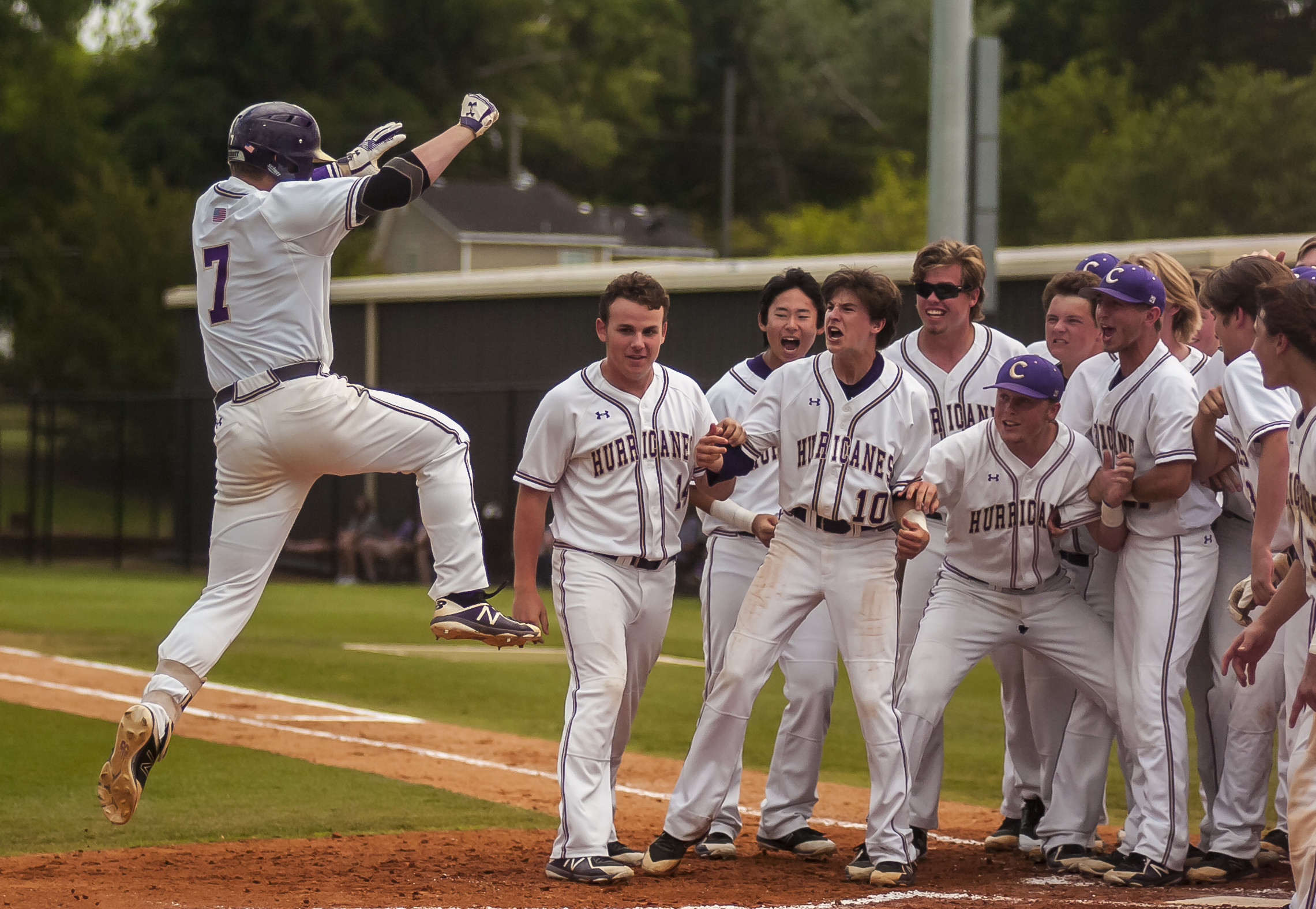 Jake Gooch is mobbed by teammates at home plate after his first-inning home run.