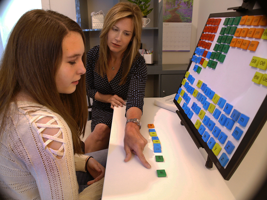 Tabitha Molina works with a client on a word builder, a tool used to help dyslexics recognize word shapes.