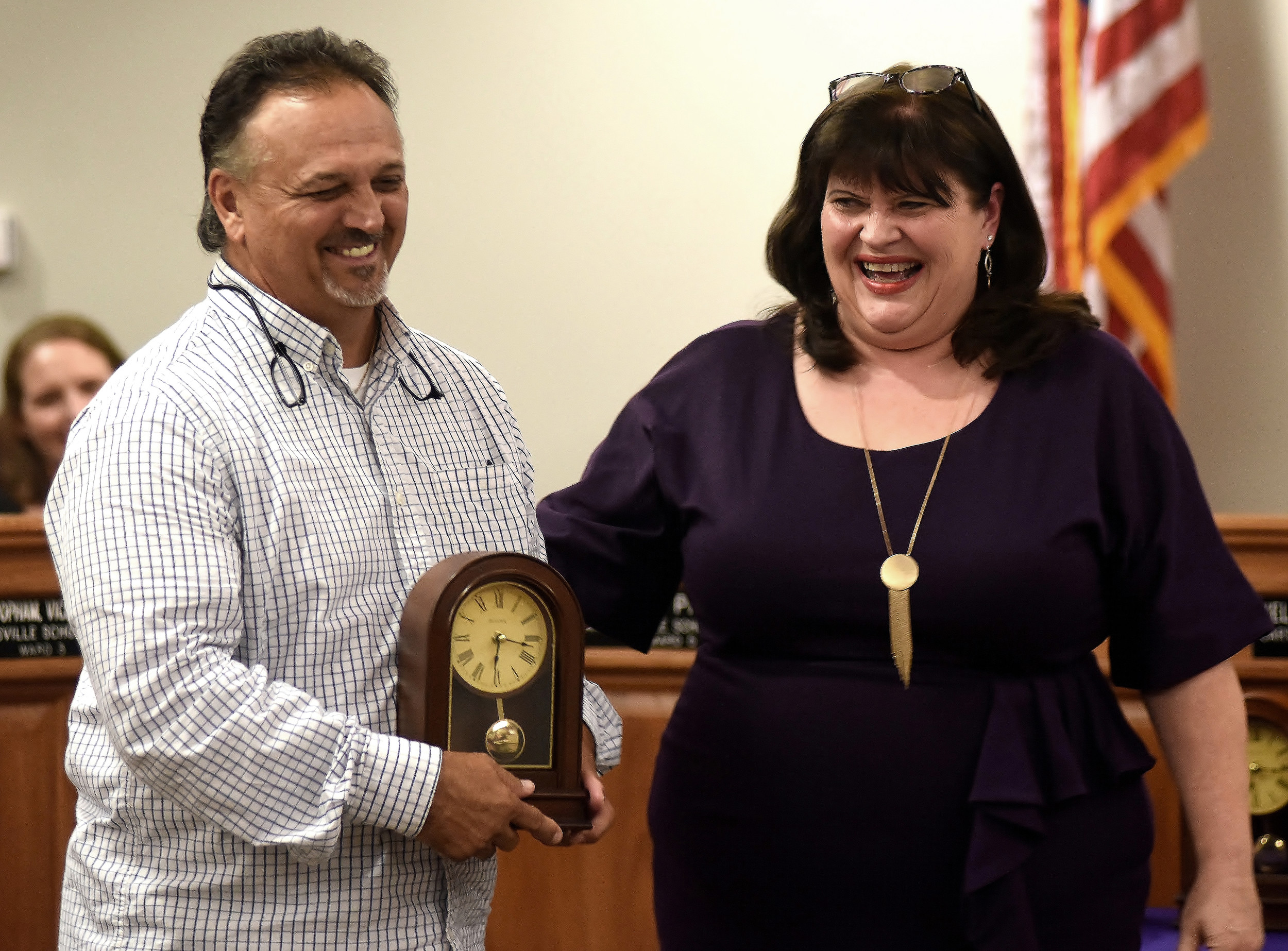 Cartersville School Board president Kelley Dial, right, shares a laugh with Cartersville High School wrestling coach Garvin Edwards as she presents him with his retirement clock at Monday's school board meeting.Edwards, with 30 years of service in education between his time with Cartersville and Armuchee, was recognized along with 17 other retirees at the meeting.