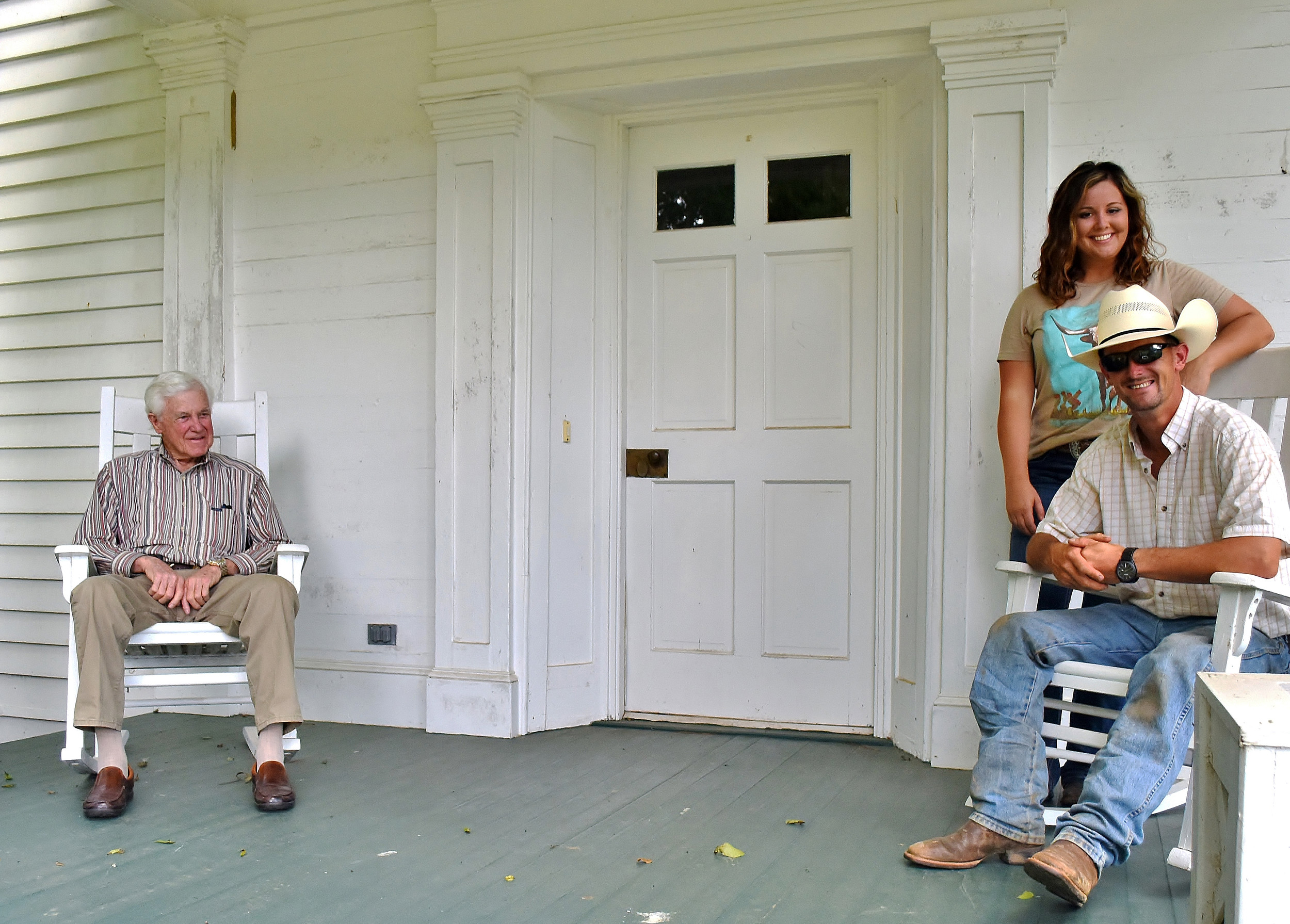 Mack Watkins, left, relaxes on his front porch with his son Jonathan and daughter-in-law, Jessica.