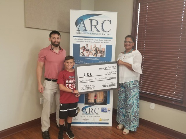 Joined by his father, Patrick Nelson, 11-year-old Colin Nelson presents a check to Allatoona Resource Center Site Coordinator Nichole Varnell.