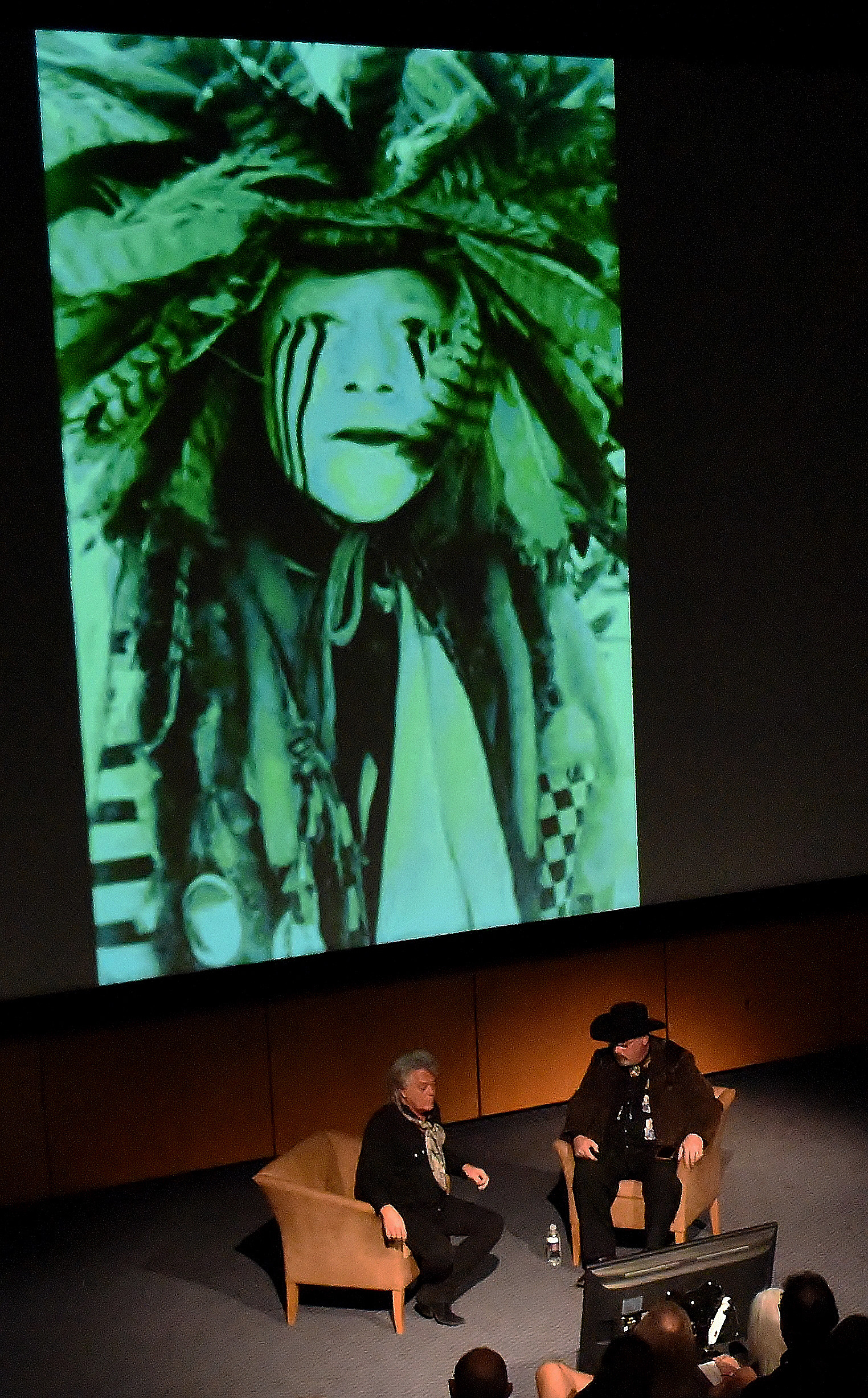 "With his image ""Lakota Dancer"" from the Badlands series projected on the screen of the Booth Museum's theatre, entertainer Marty Stuart, left, speaks with museum director Seth Hopkins during a lecture kicking off Stuart's photography exhibit ""American Ballads: The Photographs of Marty Stuart,"" which runs through November 18 at the Booth."