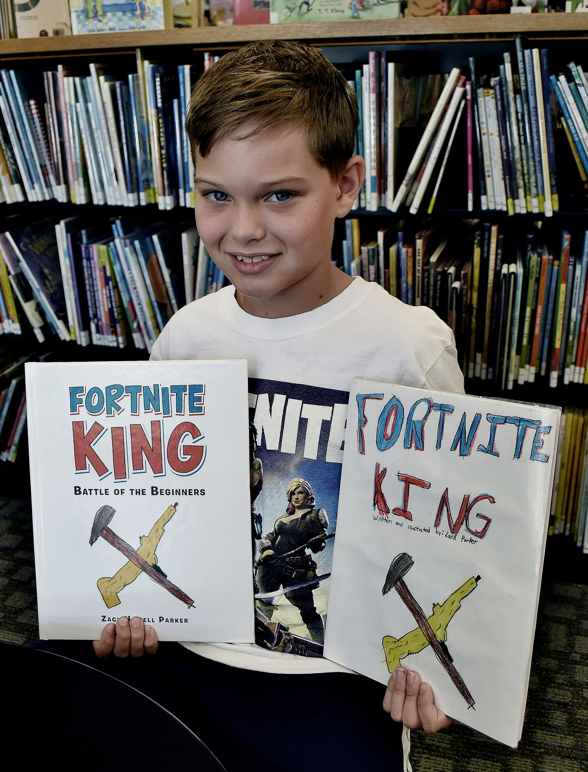 "Nine-year-old Zack Parker, of Cartersville, with the finished edition, left, and the rough draft of his recently-published book, ""Fortnite King."""
