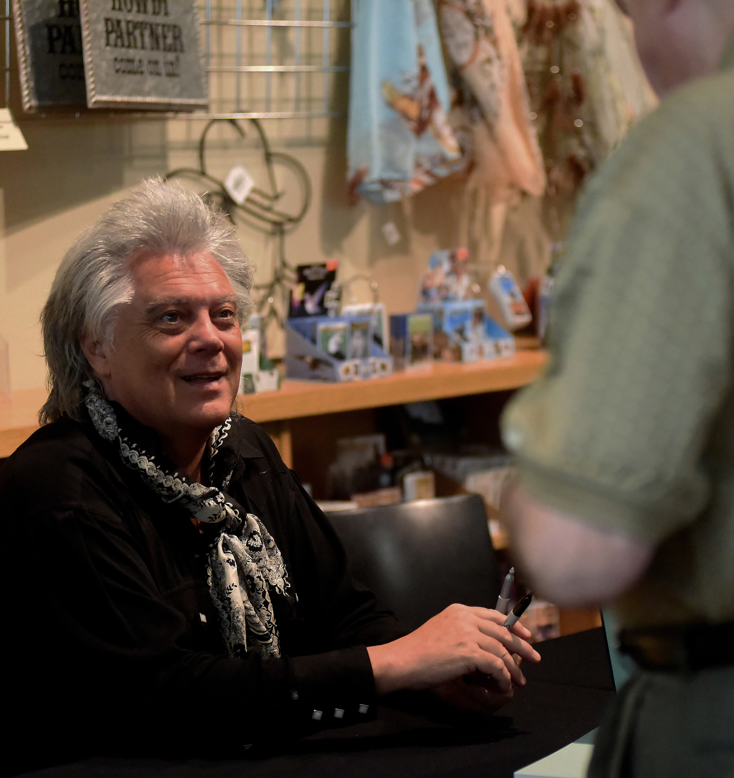 "As he signs books in the gift shop of the Booth Western Art Museum, entertainer Marty Stuart speaks with one of the many attendees of the opening of his photography exhibit ""American Ballads: The Photographs of Marty Stuart,"" which runs through November 18 at the Booth."