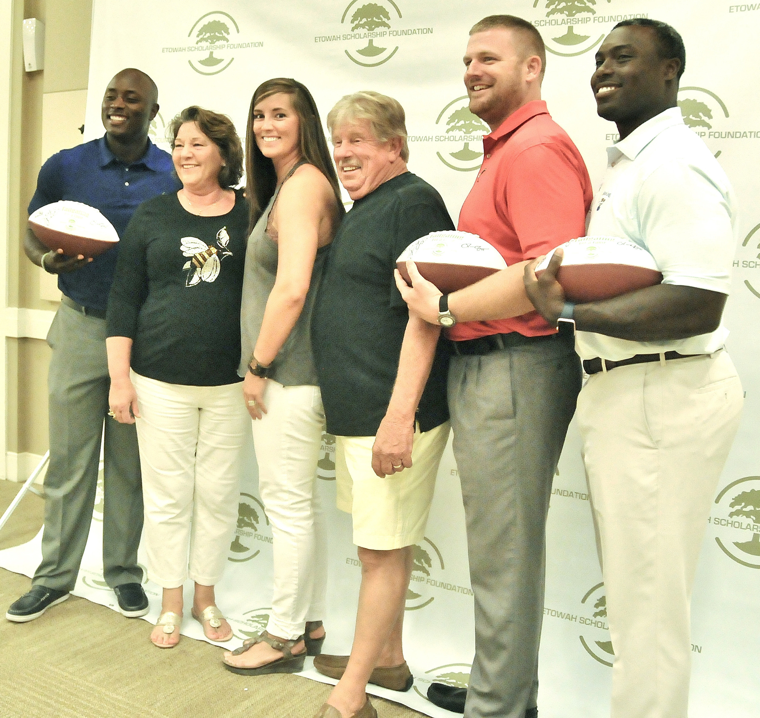 Former football players D.J. Shockley, left, Josh Brock, second from right, and Ronnie Brown, right, pose for photos with a few guests at last year's Tailgating for a Cause, a  fundraiser for the Etowah Scholarship Foundation.