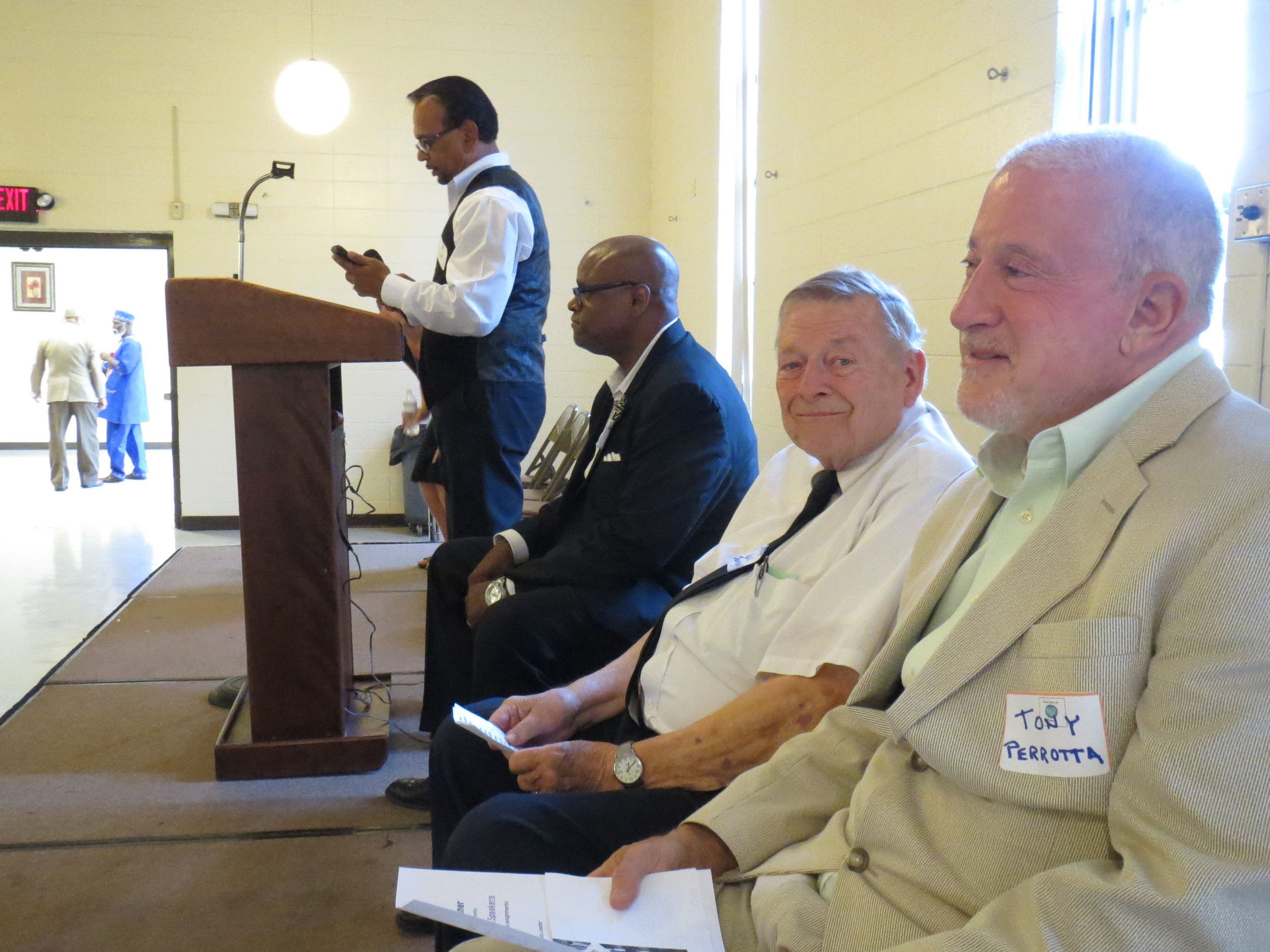 Unity Table Dinner organizer Nassim Baksh takes the podium at Saturday's event at the Cartersville Civic Center; from left to right are speakers the Rev. W.J.E. Coombs, the Rev. Louis Tonsmiere and Anthony Perrotta.