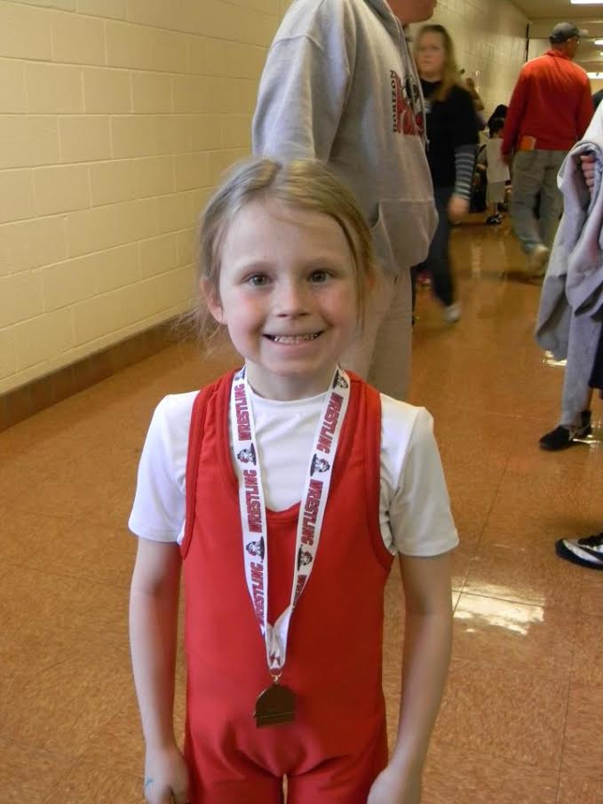 A then-7-year-old Kailey Rees poses with her bronze medal from her first-ever wrestling tournament.