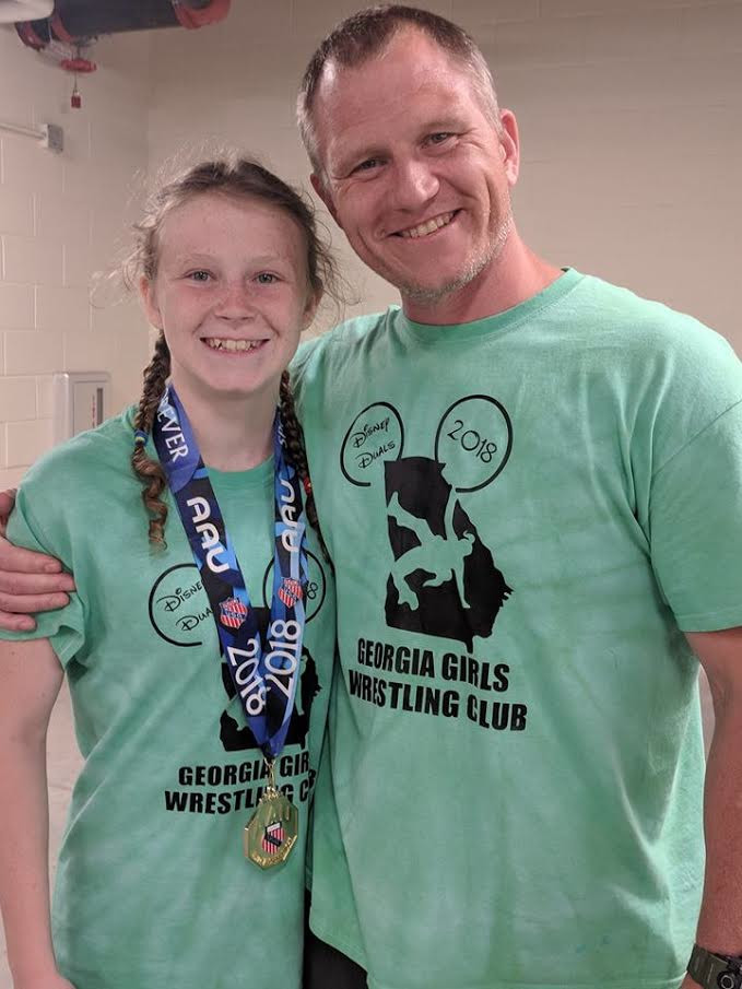 Kailey Rees poses with her father, Bryan, after earning first place in the Disney Duals by going undefeated in her weight class this summer.