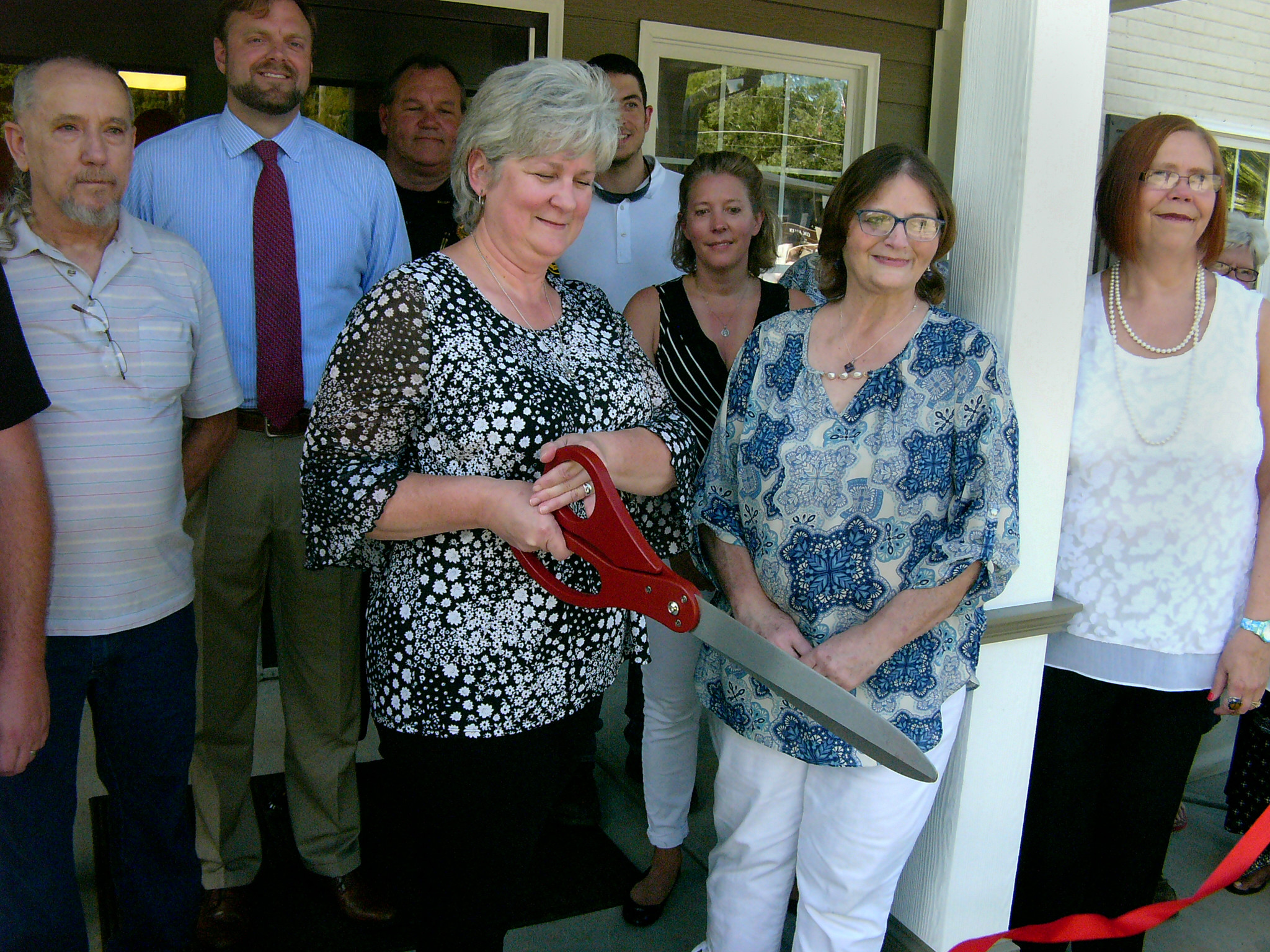 Mayor Kim Billue, surrounded by staff and elected officials, cuts the red ribbon signifying the reopening of White City Hall following repairs to the building.