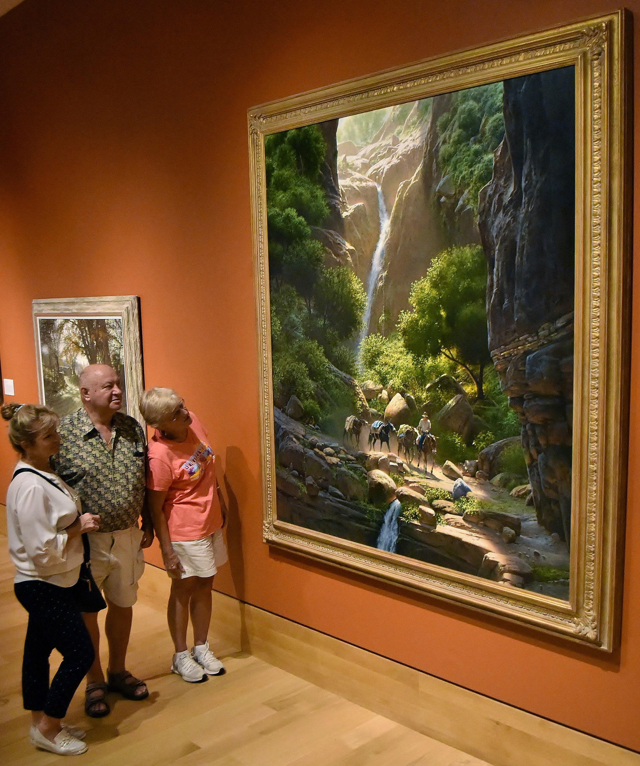 "Mariann Midi, left, visiting from Hungary, and Andrew and Kathleen Nagy of Acworth look at ""Canyon Passages,"" a painting by Bill Hughes, in the Landscape and Wildlife Gallery at the Booth Western Art Museum."