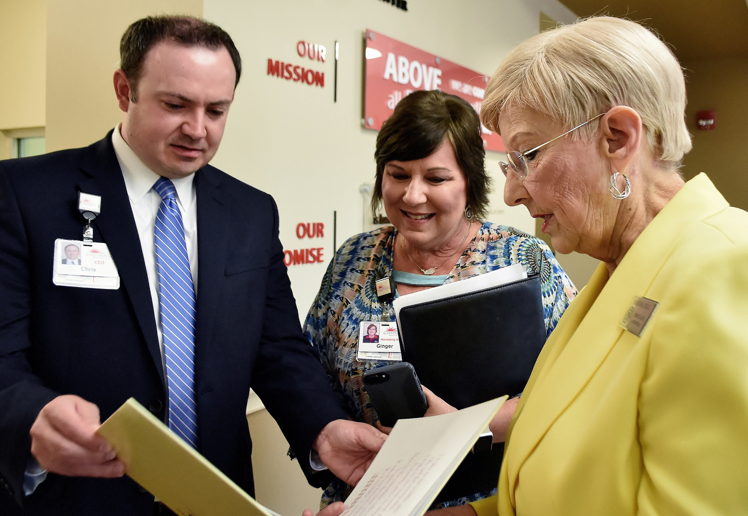 "Cartersville Medical Center CEO Chris Mosley and Director of Marketing and Public Relations Ginger Tyra look at Elizabeth Brown's book, ""Who I'd Like to Be,"" provided by Georgia First Lady Sandra Deal."