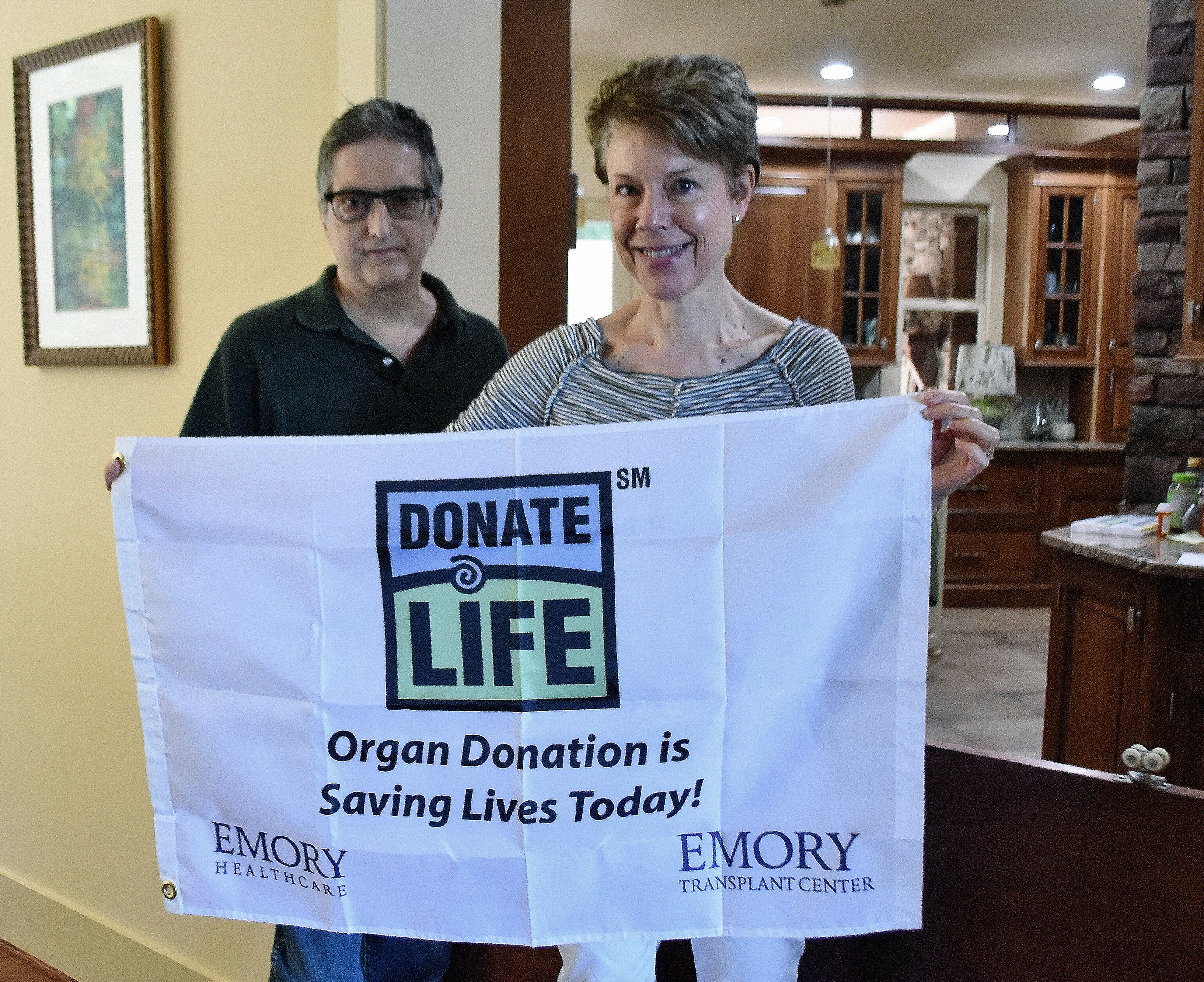 Carole Miller holds a replica of the flag that flies over the Emory Transplant Center, where she and her husband, Stuart, left, underwent their surgeries.
