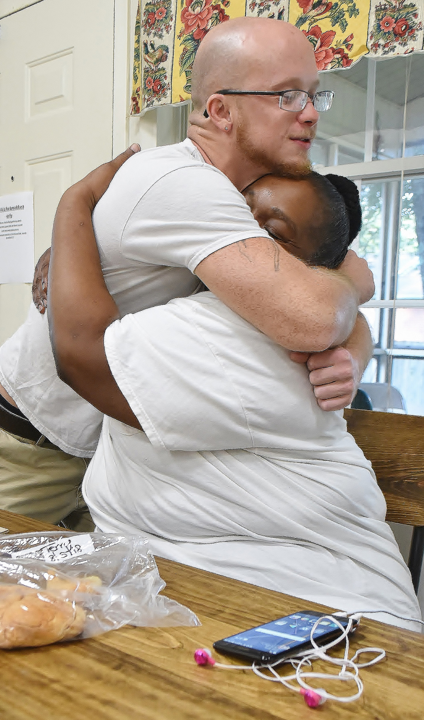 Terry, seated, a guest at the Good Neighbor Homeless Shelter in Cartersville, gets a hug from fellow guest, Bradley.