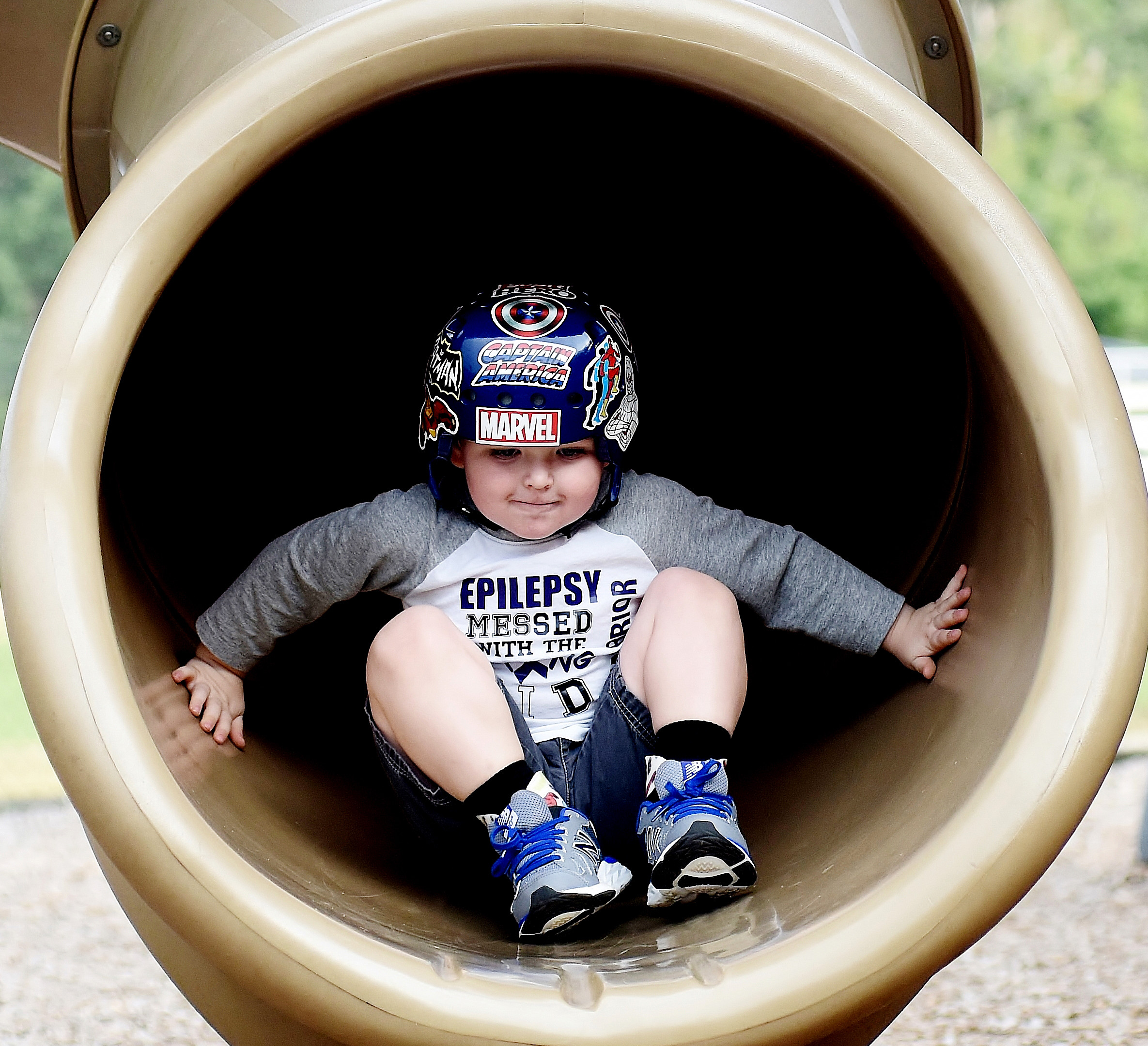 Three-year-old Cade Allen comes out a slide on one of the Dellinger Park playgrounds.